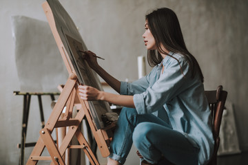 Long haired woman putting one hand on the easel while drawing