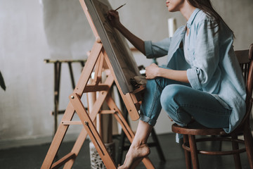 Female artist sitting with crossed legs and drawing