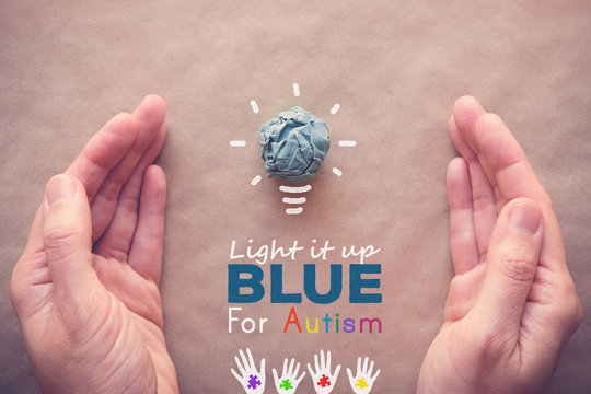 Blue paper light bulb with hands, Light it up Blue for Autism awareness