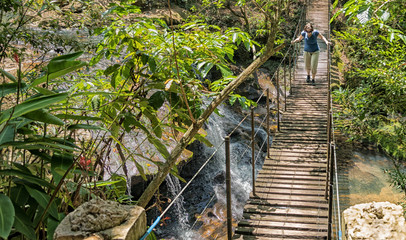 Woman on a suspension bridge over a waterfall in the rainforest of Paraguay..