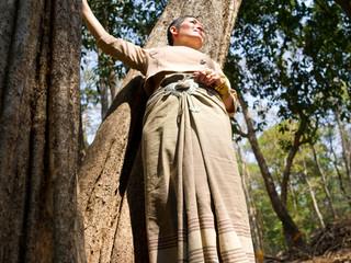 Femme  en habit traditionnel thaïlandais appuyée à un arbre au Wat Umong