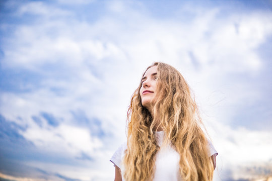 A white woman against a background of sky and clouds. the struggle for gender equality . Women force rights self-confident concept. feminism and beauty.