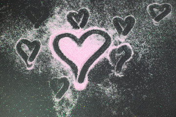 scattered pink sparkles on black background and in which the heart is painted a good gift for Valentine's Day