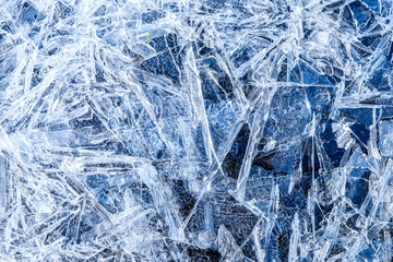 close up of dense ice crystal filled pond surface texture background on cold winter day