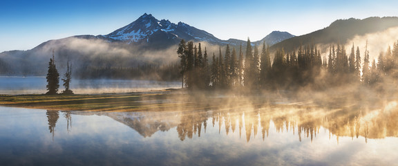 South Sister and Broken Top reflect over the calm waters of Sparks Lake at sunrise in the Cascades Range in Central Oregon, USA in an early morning light. Morning mist rises from lake into trees.