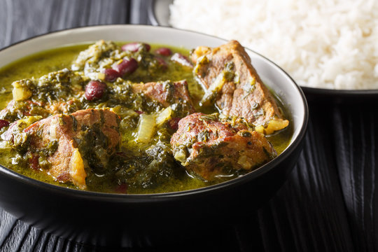 Authentic Ghormeh Sabzi dish of lamb stew meat with herbs and beans close-up in a bowl and rice. horizontal