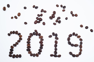 Text 2019 written by coffee beans. Royalty high-quality free stock macro photo image of shape 2019 design text by roasted black coffee beans on white background. Close-up or macro photo coffee bean