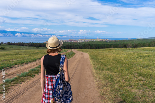 Tween tourist girl in hat and backpack walking on country road alone and  admiring picturesque landscape 5eb502f82446