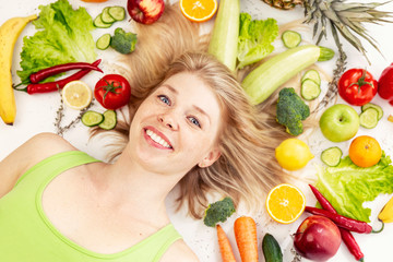 Young smiling woman lies in fruits and vegetables