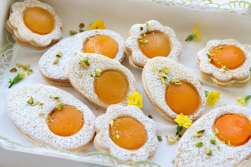 Cookies in the shape of white eggs with apricot yolk with pistachios as homemade decoration