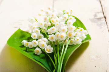 Poster de jardin Muguet de mai bouquet of lily of the valley flowers on old painted bright wood table background