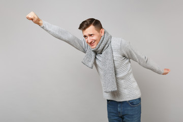 Funny young man in gray sweater, scarf with outstretched hand like Superman isolated on grey wall background. Healthy fashion lifestyle people sincere emotions cold season concept. Mock up copy space.