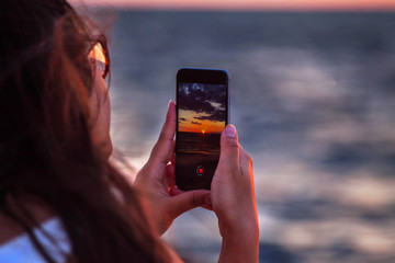 woman's hand holding smart phone to taking sunset time lapse on the beach. mobile phone with view on screen at sunset