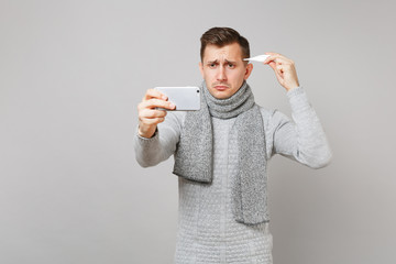 Upset young man in gray sweater, scarf holding thermometer, doing selfie shot on mobile phone, making video call isolated on grey background. Health ill sick disease treatment, cold season concept.