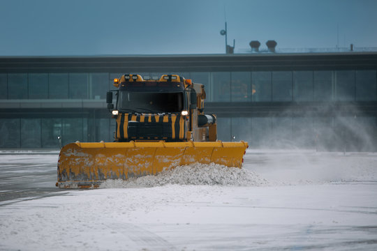 Snowplow removing snow from runways and roads in airport during snow storm