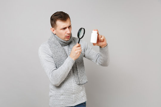 Young man in sweater, scarf holding, looking on medication tablets, aspirin pills in bottle behing magnifying glass isolated on grey background. Health, ill sick disease treatment cold season concept.