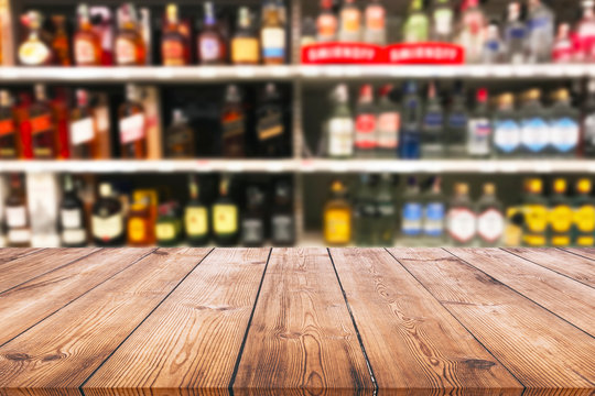 Wood table top and wine Liquor bottle on shelf blurred background