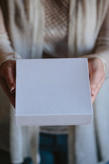 Woman's hands hold a white blank box with wedding handmade jewelry inside