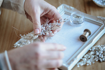 Closeup macro photo of details, workplace of decorator and creator of wedding imitation jewelry. Woman's hands in a process of creation