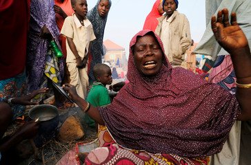 An internally displaced woman prepares breakfast as she camps at the Teachers village camp in Maiduguri
