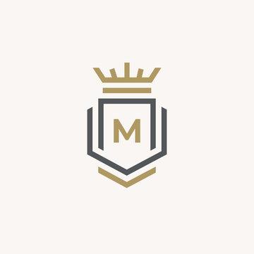 Heraldic Letter M monogram. Elegant minimal logo design. Letter M + Crown + Book + Shield.