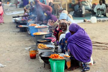 Internally displaced women vendors fry beans cake at the Teachers village camp in Maiduguri