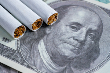 Classic cigarettes are on the hundred dollar bills US. Close up.