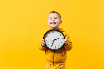 Little kid boy 3-4 years old wearing yellow clothes hold clock isolated on orange wall background, children studio portrait. People sincere emotions, childhood lifestyle concept. Mock up copy space.