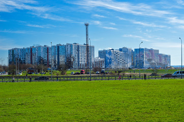 Green lawn and modern apartment buildings. City skyline. Walking zone, comfortable residential quarters. Sunny spring weather. St. Petersburg, Russia, 1 May 2018