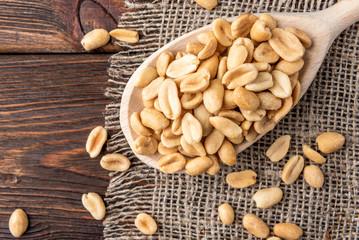 Salt peanut on dark wooden background.