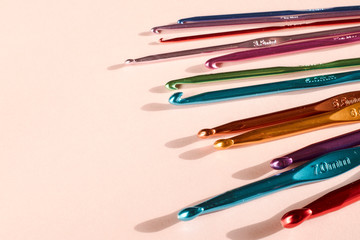 A set of multicoloured crochet hooks on a pink background