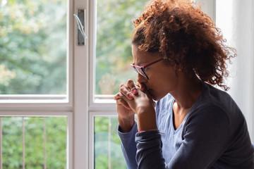 Portrait of pensive black woman standing beside window Wall mural
