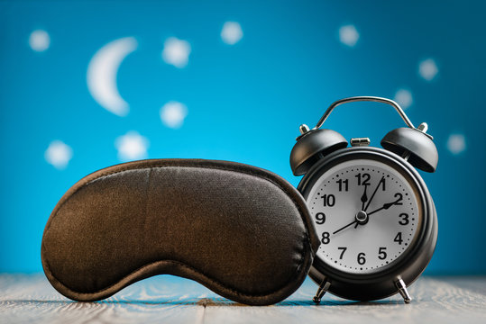 Eye mask and alarm clock