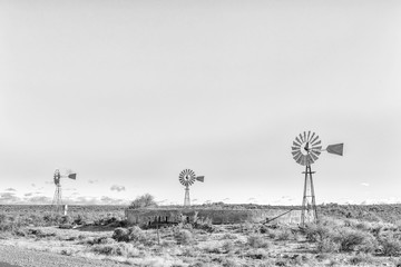Monochrome landscape with three water-pumping windmills and dam