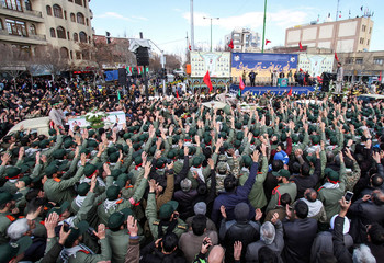 Members of Iran's elite Revolutionary Guards, gather around the coffins of their fellow guards, who were killed by a suicide car bomb, during the funerals in Isfahan