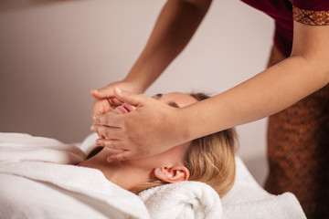 female client recieving head massage in the beauty salon. close up cropped photo