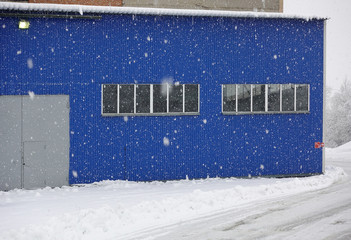 Snowfall on the background of an industrial warehouse of blue metal.