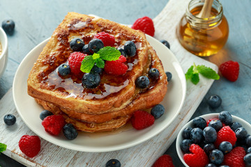 French cinnamon toast with blueberries, raspberries, maple syrup and coffee. morning breakfast