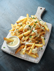 Homemade Baked Potato Fries with cheese sauce on white wooden board