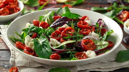 Sun dried tomatoes Salad with fresh vegetables mix and mozzarella cheese. healthy food. closeu up