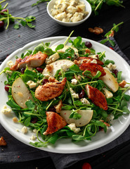 Pear, chicken salad with blue cheese, cranberry and walnuts. concept healthy food. black background