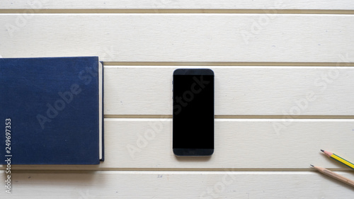 Wall mural top view with notebook and smart phone on wood background