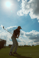 Man playing golf and hitting a golf ball at sunny day