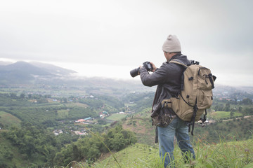 Photographer hand holding camera and standing on top of the mountain  in nature. Travel concept. Vintage tone.
