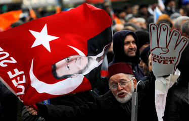 A supporter of Turkish President Tayyip Erdogan waves a flag during a rally for the upcoming local elections in Istanbul