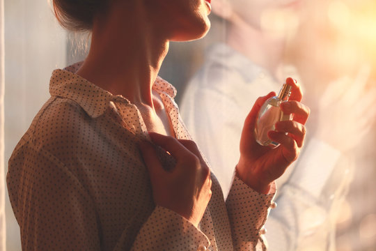 Stylish woman in blouse spraying a bottle of favorite perfume at sunset. Fashion, beauty and style