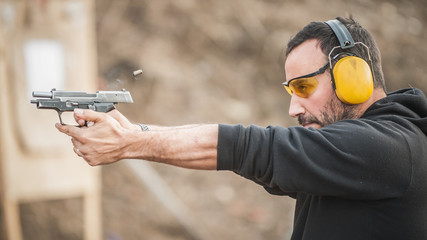 Shooter holding gun and training tactical shooting. Close-up detail view