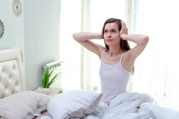 Young woman suffering and disturbed by noisy neighbors and covering her ears with hands while trying to sleep in bed at home in early morning