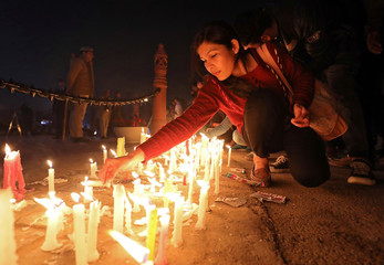 A woman lights candles during a vigil to pay tribute to CRPF personnel who were killed after a suicide bomber rammed a car into the bus carrying them in south Kashmir on Thursday, in front of India Gate war memorial in New Delhi