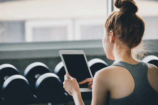 Fitness woman using tablet after exercise in gym